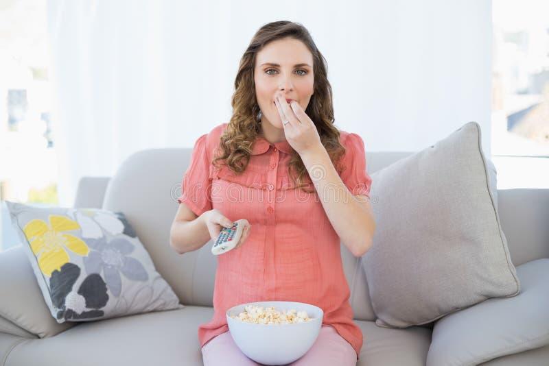 Donna incinta sveglia che mangia popcorn mentre guardando televisione immagini stock libere da diritti