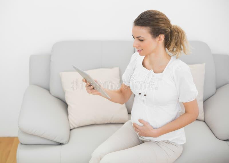 Donna incinta sveglia che tocca la sua pancia mentre per mezzo della sua compressa fotografia stock libera da diritti