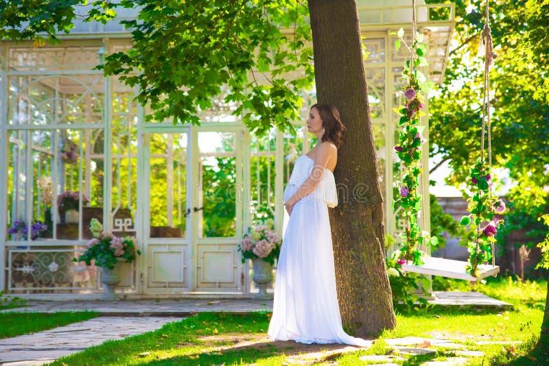 Donna incinta in vestito bianco sul prato inglese della natura con il gazebo con i fiori immagini stock