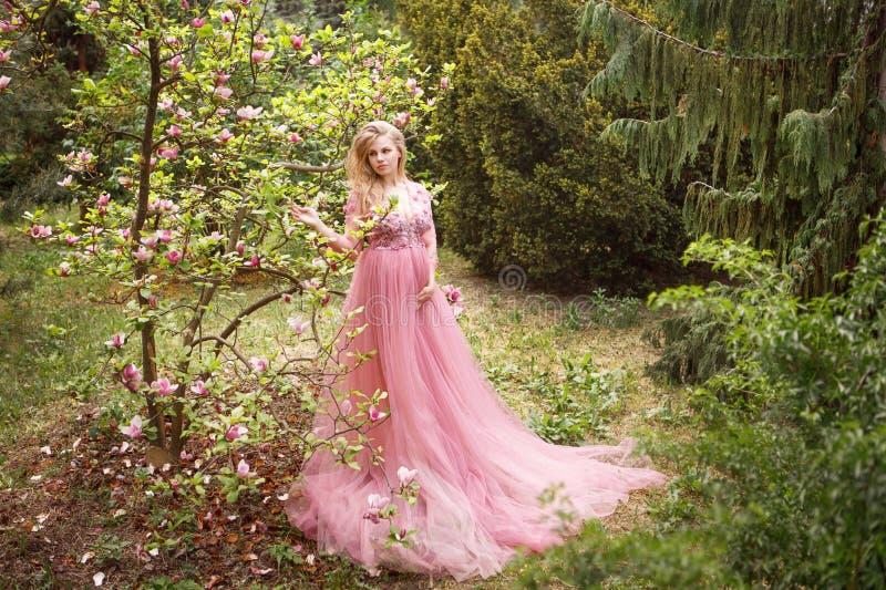 Donna incinta in vestito lungo rosa che sta nella magnolia di fioritura in foresta fotografie stock