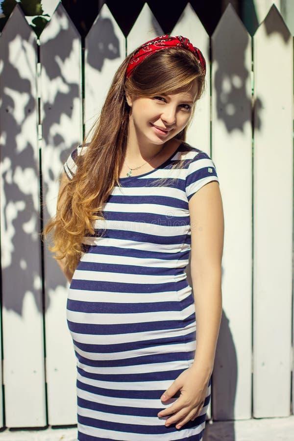 Donna incinta in vestito a strisce che posa all'aperto immagini stock