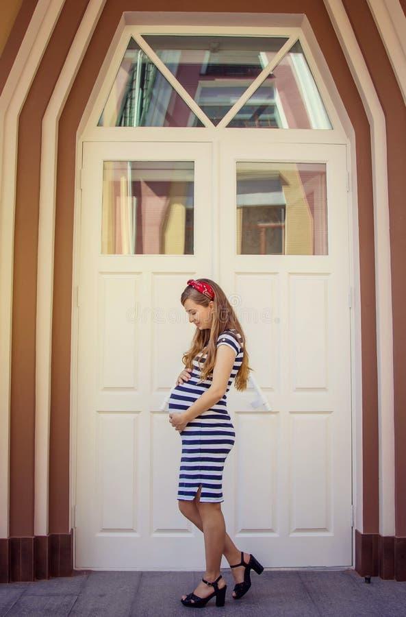 Donna incinta in vestito a strisce che posa all'aperto immagine stock libera da diritti
