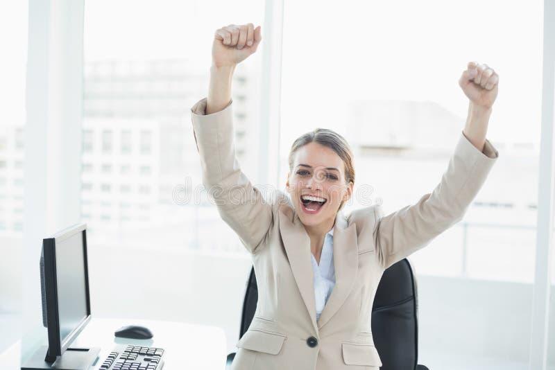 Donna incoraggiante felice che la alza braccioli che si siedono sulla sua poltrona girevole immagini stock