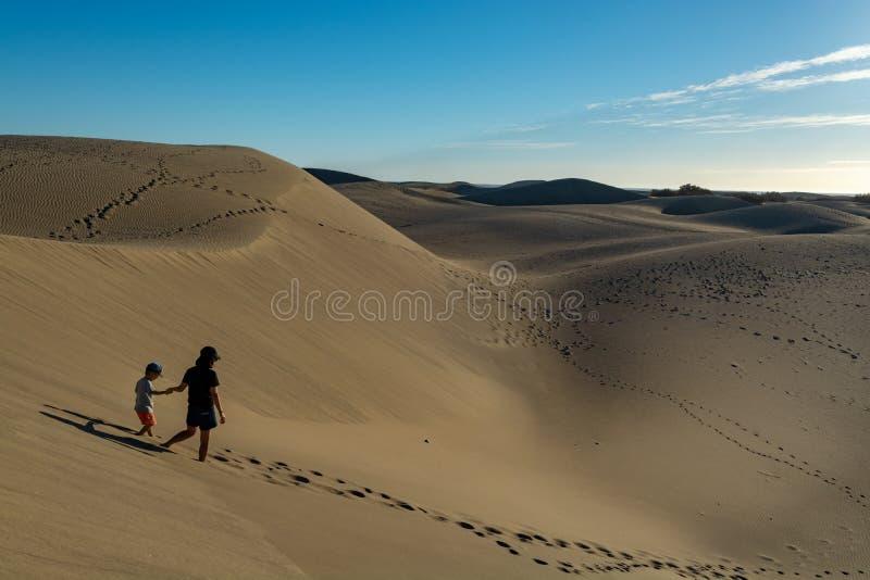 Donna indefinita e bambino che camminano in dune sabbiose gialle di Maspalomas, Gran Canaria, Spagna immagine stock