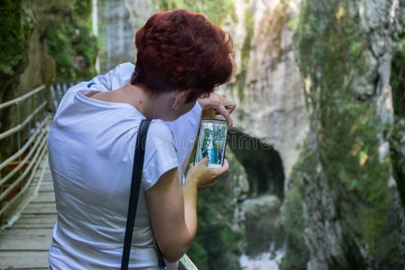 Donna indefinita fare foto mobile di belle gole du Fier, canyon francese vicino ad Annecy fotografia stock