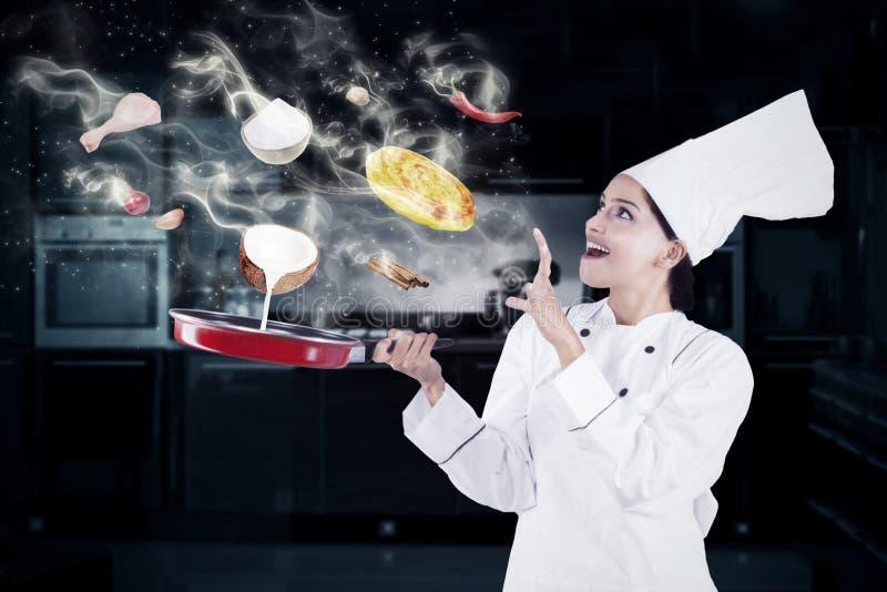 Donna indiana che cucina con la magia fotografia stock