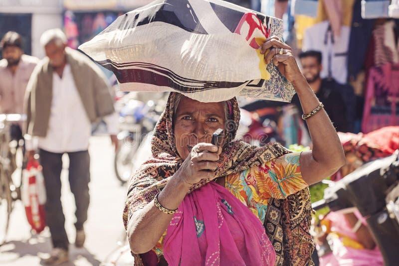 Donna indiana con il suo acquisto del cellulare al mercato di verdure con una borsa sulla sua testa immagini stock