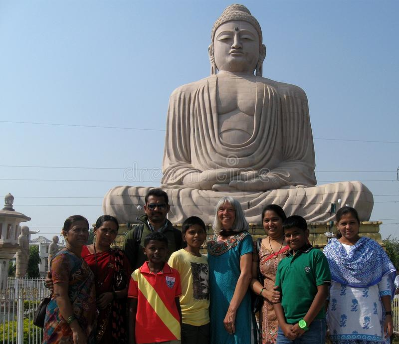 Donna indiana del Caucasian della famiglia della grande statua di Buddha immagine stock