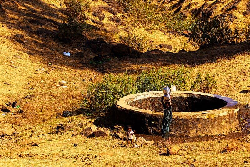 Donna indiana del villaggio che prende bene la forma dell'acqua immagine stock
