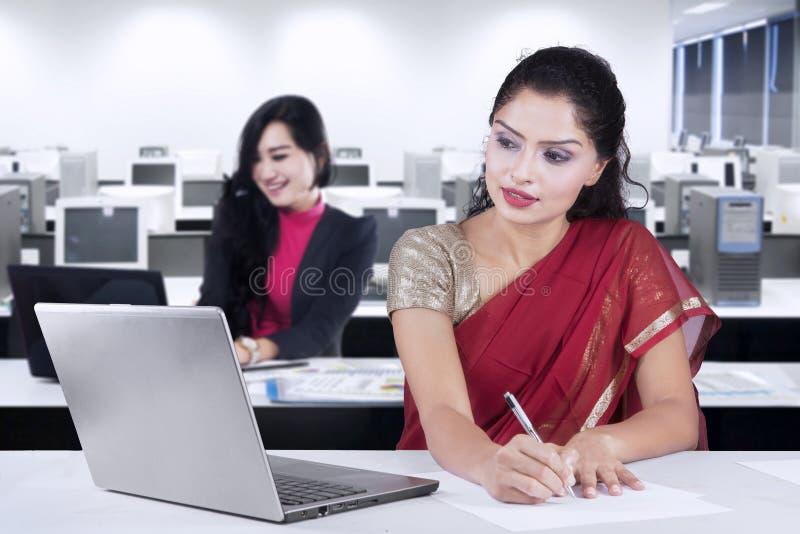 Donna indiana e suo il partner che lavorano nell'ufficio fotografia stock libera da diritti