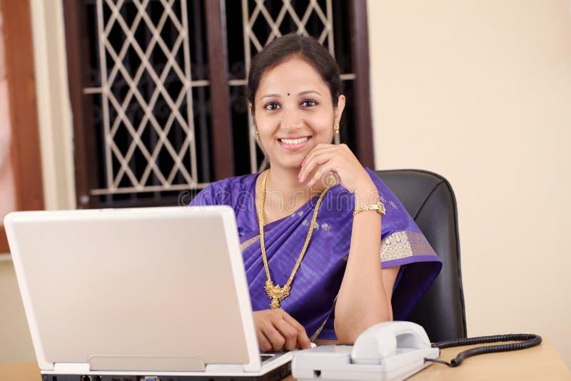 Donna indiana sorridente sul lavoro fotografia stock