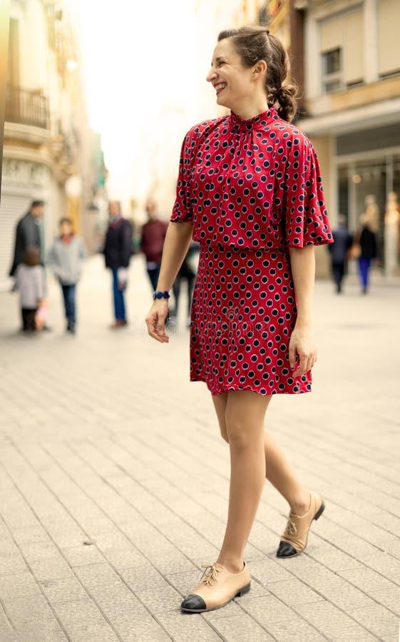 Donna indipendente vestita nel rosso che ride molto con le emozioni positive fotografia stock