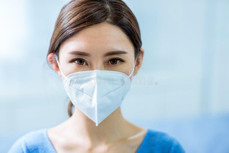 Donna indossa una maschera del volto fotografie stock libere da diritti