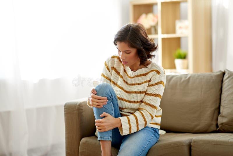 Donna infelice che soffre dal dolore in gamba a casa immagini stock libere da diritti