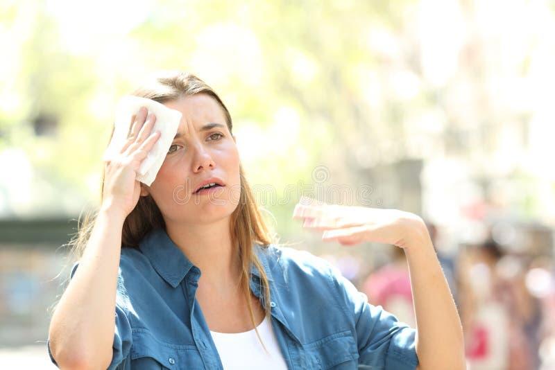 Donna infelice che suda soffrendo un colpo di calore fotografia stock libera da diritti