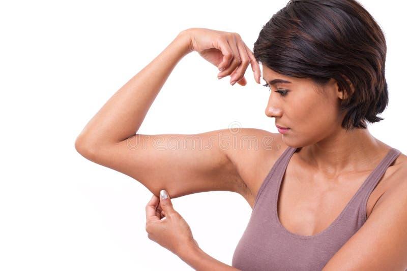 Donna infelice con la mano che giudica eccessivo braccio grasso fotografie stock