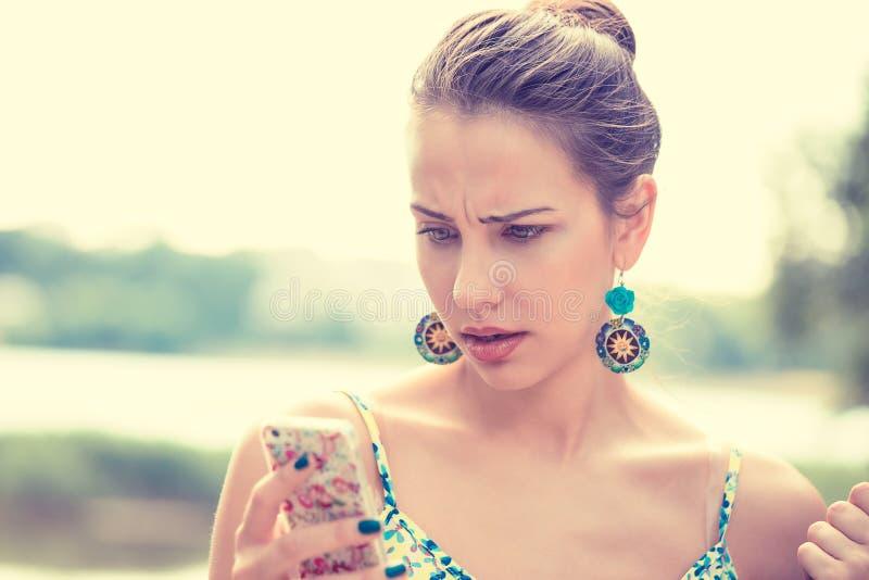 Donna infelice scettica triste turbata che manda un sms sul telefono immagini stock libere da diritti