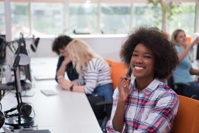 Donna informale afroamericana di affari che lavora nell'ufficio fotografie stock