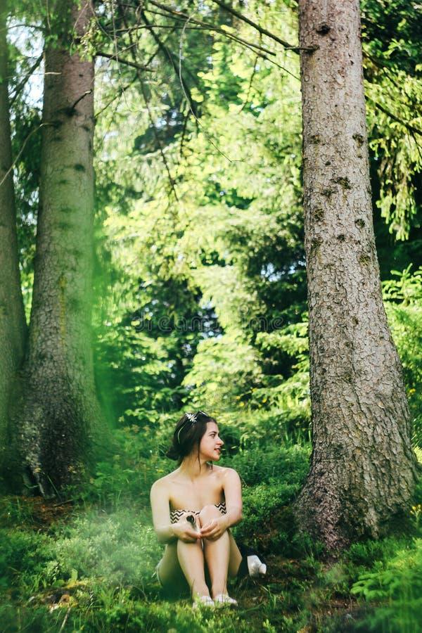 Donna innocente felice che si siede nella foresta atmosferica verde sul fondo delle montagne di estate fotografie stock libere da diritti