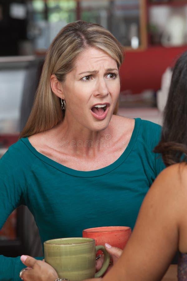Donna insultata con l'amico in caffè immagini stock