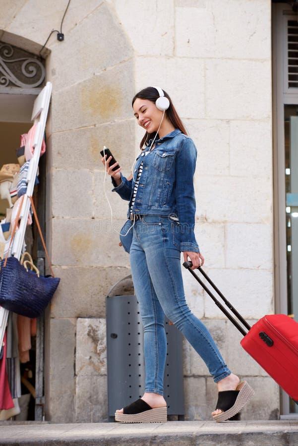 Donna integrale che cammina fuori con i bagagli e le cuffie fotografia stock