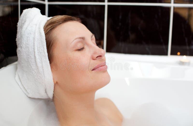 Donna intelligente che si distende in un bagno di bolla fotografia stock