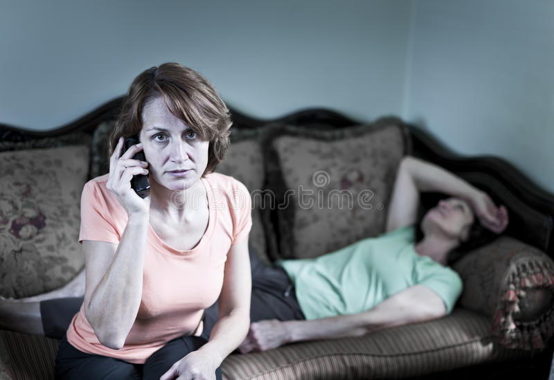 Donna interessata con la madre ammalata immagini stock libere da diritti