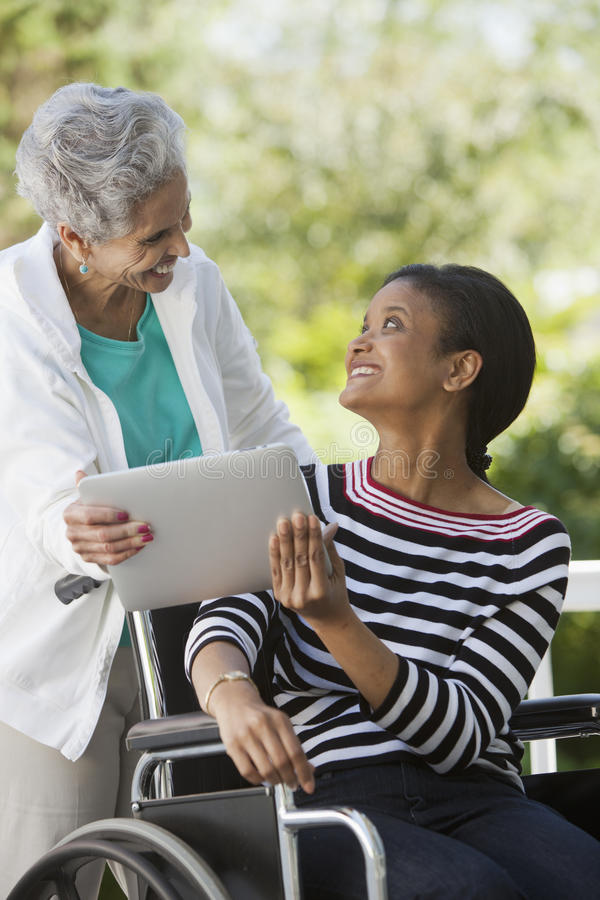 Donna invalida in una sedia a rotelle con la sua madre immagini stock