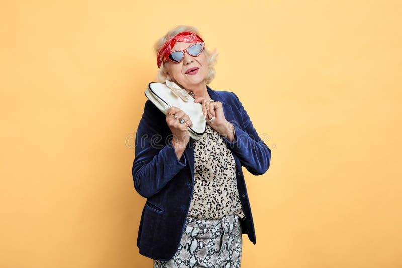 Donna invecchiata allegra in occhiali da sole che esaminano la macchina fotografica immagine stock libera da diritti