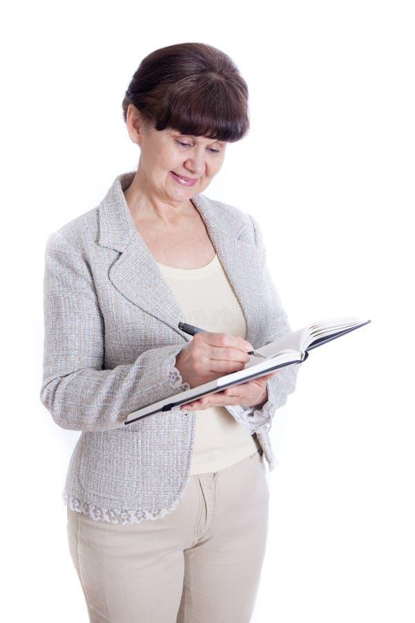 Donna invecchiata che posa come un impiegato di concetto, amministratore, segretario Ritratto contro di fondo bianco fotografia stock