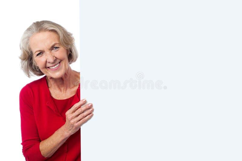 Donna invecchiata che tiene il bordo in bianco dell'annuncio immagine stock