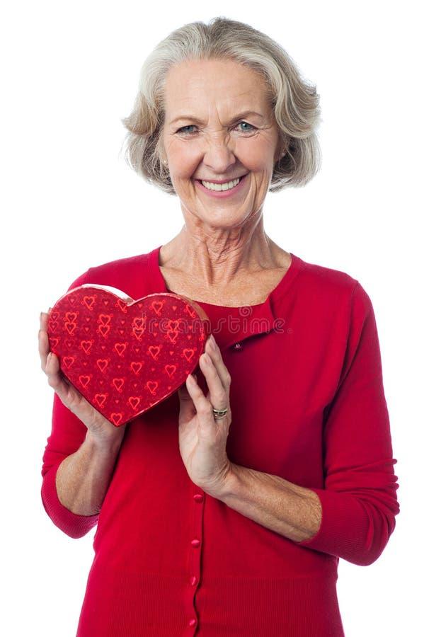 Donna invecchiata che tiene un contenitore di regalo rosso del biglietto di S. Valentino fotografia stock