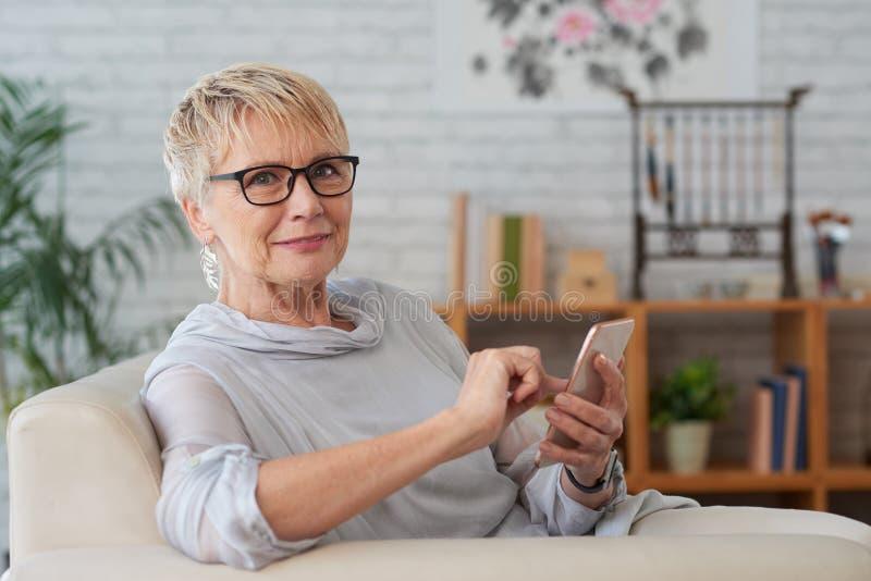 Donna invecchiata con lo smartphone fotografia stock