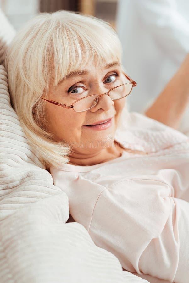 Donna invecchiata contentissima piacevole che si trova a letto immagini stock