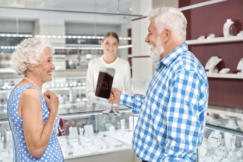 Donna invecchiata elegante che prova sulla collana della perla alla gioielleria fotografia stock libera da diritti