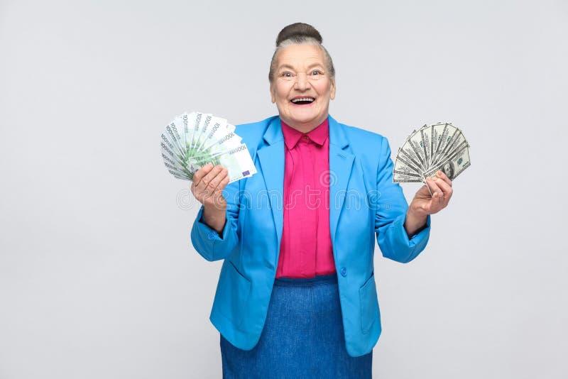 Donna invecchiata felice tenendo molta euro ed i dollari fotografie stock libere da diritti