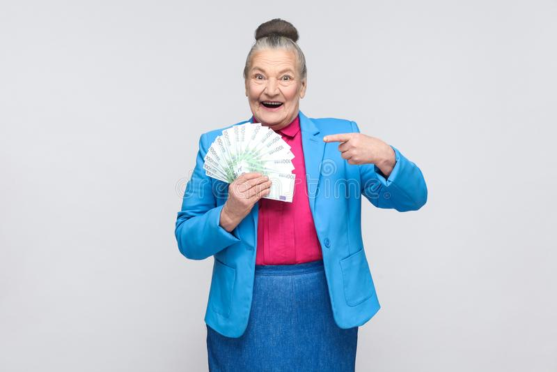 Donna invecchiata felice tenendo molta euro ed indicando dito fotografie stock