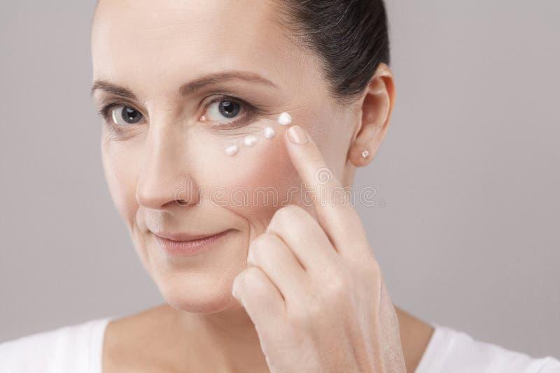Donna invecchiata media con la pelle perfetta del fronte che applica crema cosmetica con il dito su pelle vicino agli occhi e che immagine stock