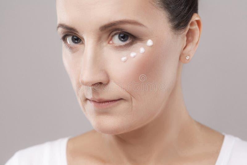Donna invecchiata media con la pelle perfetta del fronte che applica crema cosmetica su pelle vicino agli occhi e che esamina mac immagini stock libere da diritti