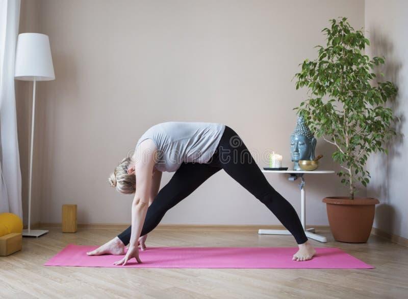 Donna invecchiata mezzo che fa yoga all'interno immagine stock libera da diritti