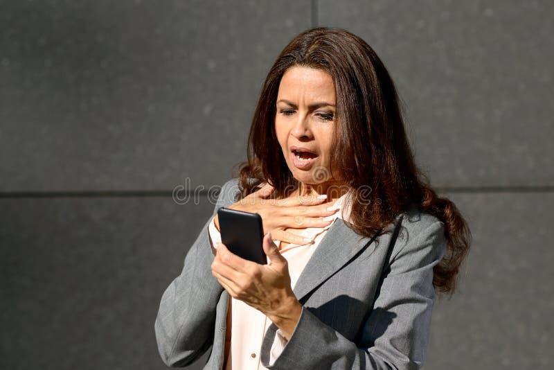 Donna invecchiata mezzo colpita che legge un messaggio di testo fotografie stock libere da diritti