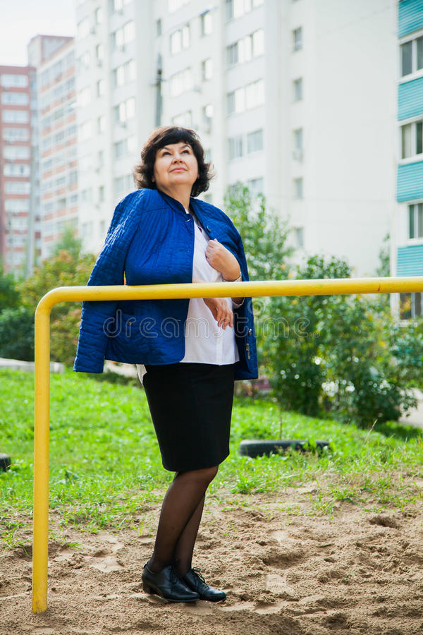 Donna invecchiata mezzo fra le costruzioni di appartamento della città fotografie stock libere da diritti