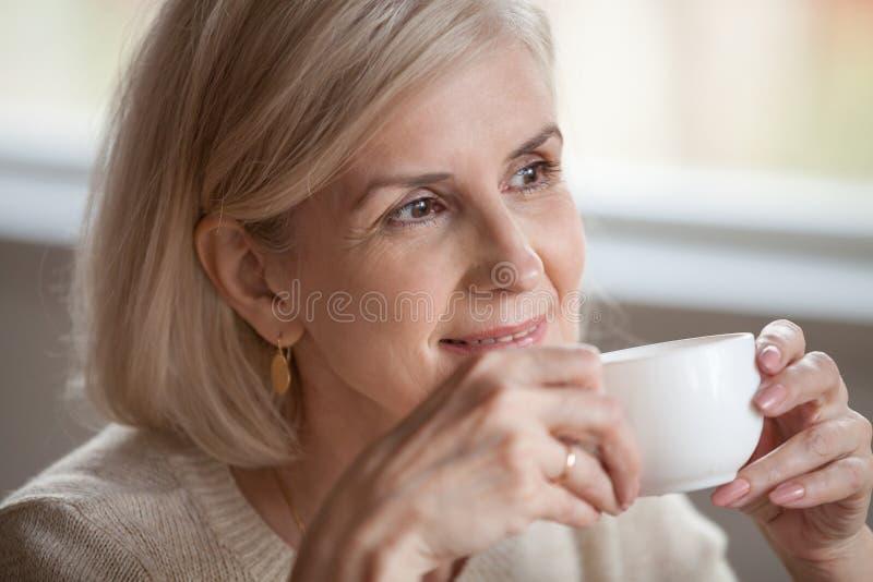 Donna invecchiata mezzo sorridente premurosa che distoglie lo sguardo sognante bevanda fotografia stock libera da diritti