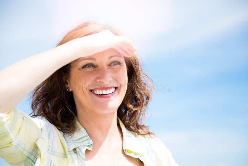 Donna invecchiata midle felice che protegge dal sole fotografia stock