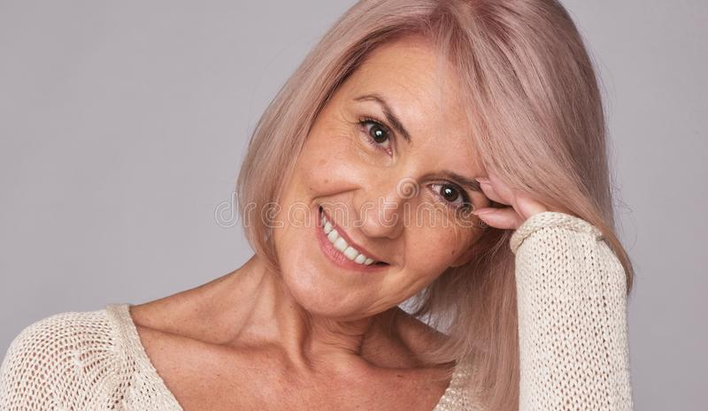 Donna invecchiata sorridente di bellezza metà di fotografia stock libera da diritti