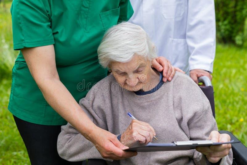 Donna invecchiata in una sedia a rotelle con assistenza medica immagine stock libera da diritti