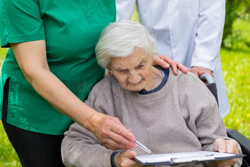 Donna invecchiata in una sedia a rotelle con assistenza medica immagini stock