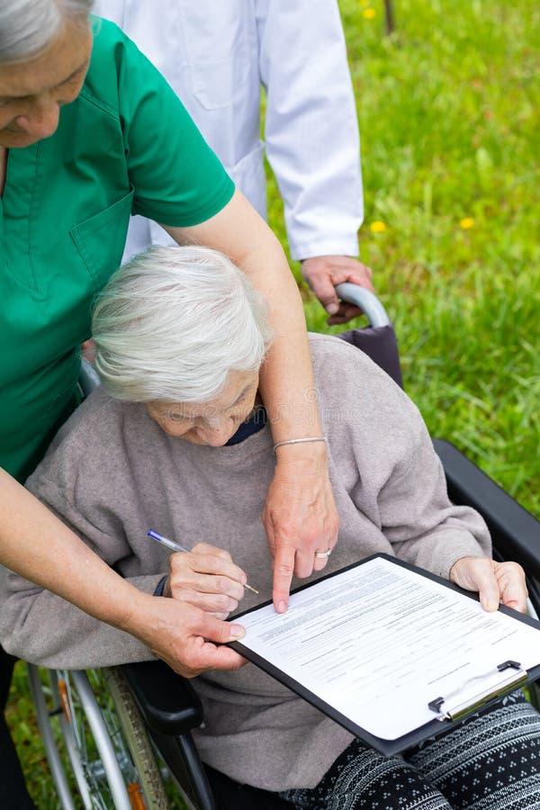 Donna invecchiata in una sedia a rotelle con assistenza medica fotografie stock