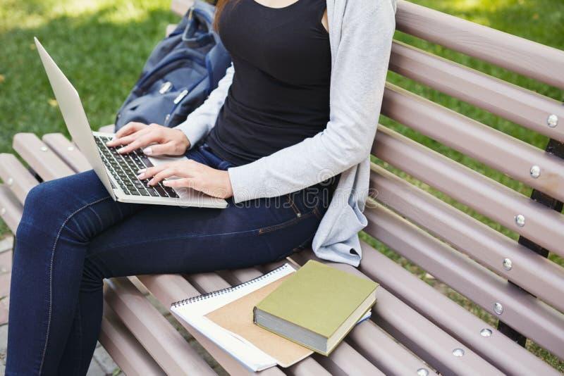 Donna irriconoscibile che scrive sul computer portatile all'aperto immagine stock libera da diritti