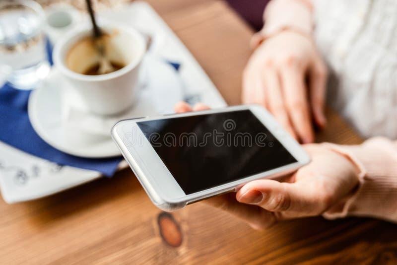 Donna irriconoscibile con lo smartphone in caffè bevente del caffè immagine stock